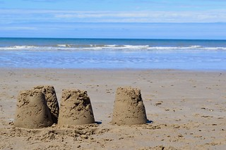 Sandcastles on a beach in Dinas Dinlle | by One Small Human