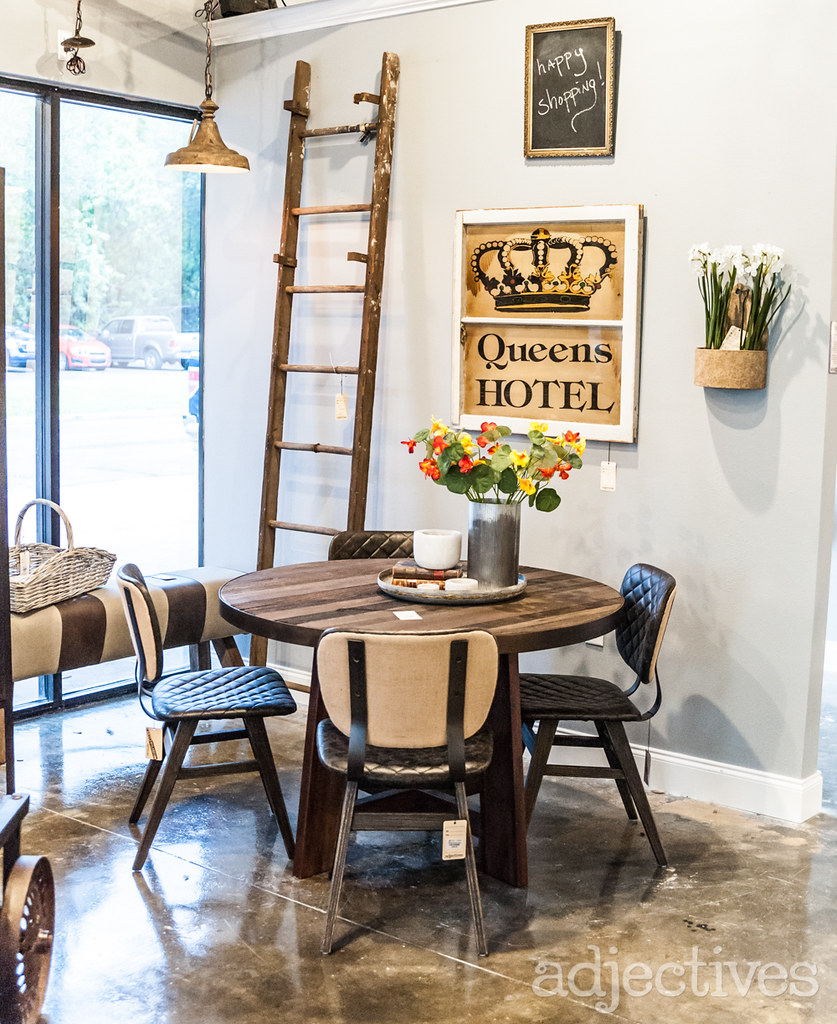 Round wood dining table, vintage kitchen decor, and wood ladder at Adjectives Altamonte