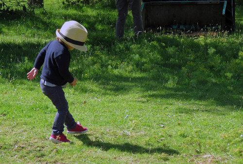 A little girl in a too big hat dances on the grass at the Jumieges Abbey Ruins in France