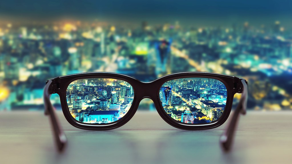 A photo of a pair of glasses against a cityscape