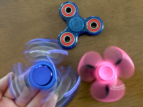 3 Fidget Spinners (hand holds one of them spinning) | by JoanDragonfly