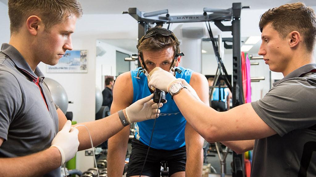 Three men in lab measuring breathing during exercise on bike