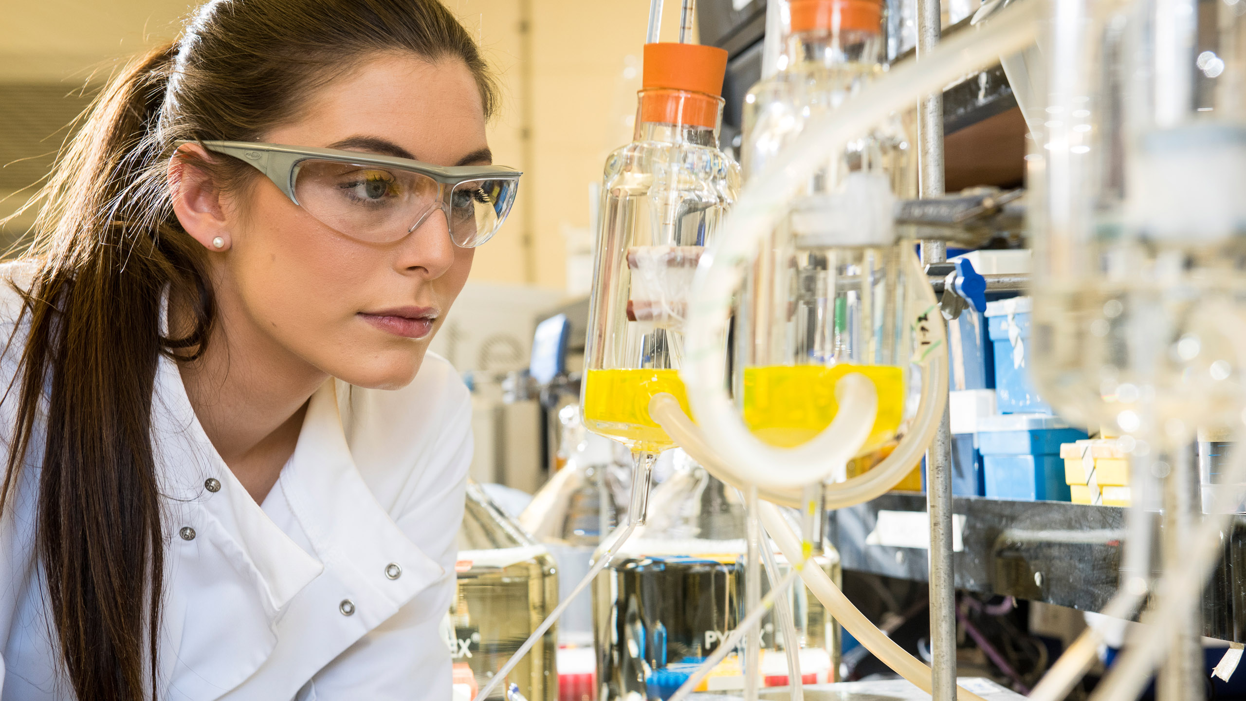 A female student with long dark hair and protective goggles in a drug discovery laboratory filled with glass vials and plastic pipes.