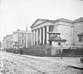 """Large public building, railings, steps, 6 columns in portico, 2 guns on plinths, one plinth inscribed India"" is Tralee Courthouse"