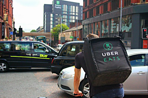 UBER Eats Delivery Cyclist Riding Through a Busy Oxford Road in Manchester | by shopblocks