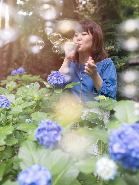 Young woman blowing bubbles in hydrangea garden