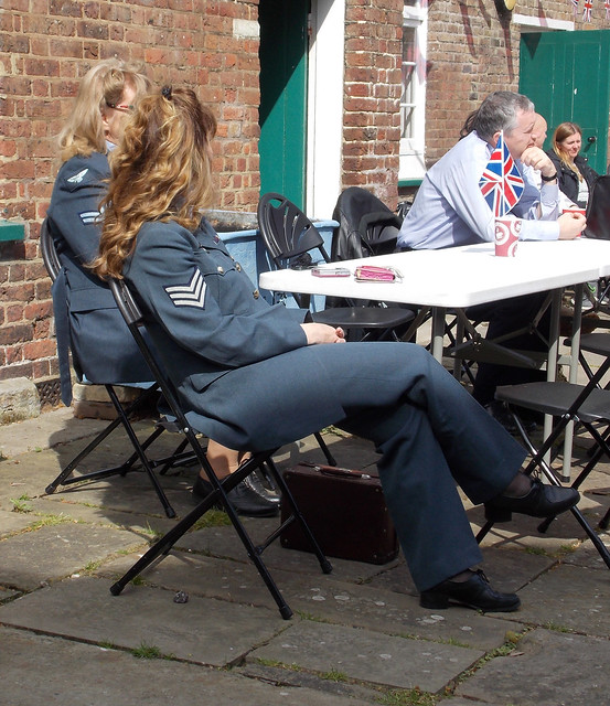 LADY SENTIMENTAL JOURNEY  SINGER ENTERTAINERS  RE-ENACTORS SITTING TAKING A BREAK AT A TABLE IN RAF SECOND WORLD WAR   UNIFORM IN THE EVENT STREET CAFE AREA VE DAY EVENT AT THE ROYAL GUNPOWDER MILLS 2017 IN A LONDON BOROUGH  SUBURB ENGLAND  DSCN0081
