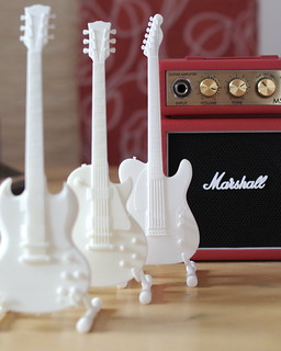 Guitars 3d printed in front of a Mini Marshall