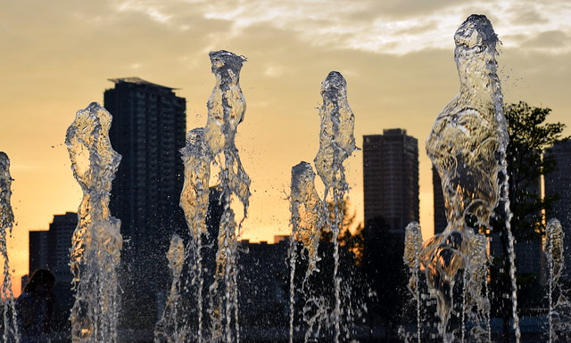 The fountains competing with the skyscrapers .  Can you spot the girl ?