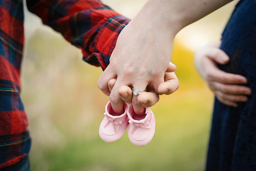 Couple holding hands with a baby's shoes | by monpetitchouphotography