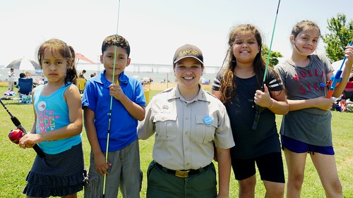 Photo of ranger with youths holdling fishing rods at Sandy Point State Park