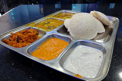 A metal tray with compartments, sitting on a shiny black table.  The largest compartment is filled with three white spongy discs.  Two others contain a soupy light brown curry with bits of vegetables visible.  The remaining three are filled with chutneys: a dry one garnished with a piece of dried red chilli, a wet light brown one, and a white coconut-based one.