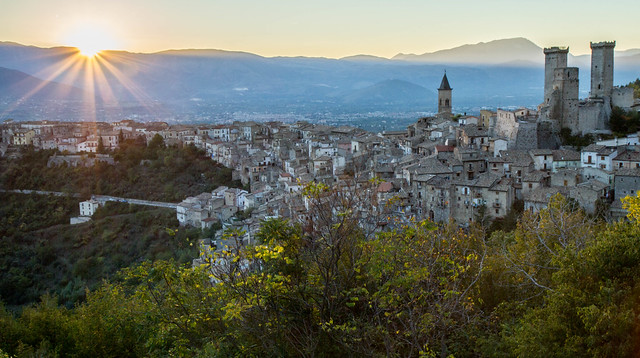 Pacentro sunset rays with castle towers and church. Abruzzo, Italy