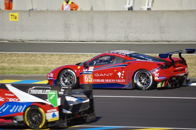 Scuderia Corsa's Ferrari 488 GTE is passed by an LMP2 as it comes out of the pits