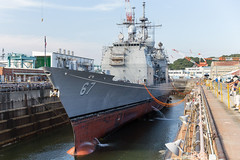 In this file photo, water is drained from a dry dock at U.S. Naval Ship Repair Facility and Japan Regional Maintenance Center (SRF JRMC) Yokosuka preparing USS Shiloh (CG 67) for a 2015 maintenance availability. (U.S. Navy/Lt.j.g. William McGough)