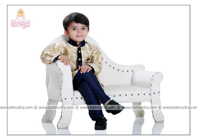 Very Cute Kid sitting on a white sofa Posing for Camera in Sherwani dress in Balmudra Studio Pune shoot done by Photographer Shrikrishna Paranjpe