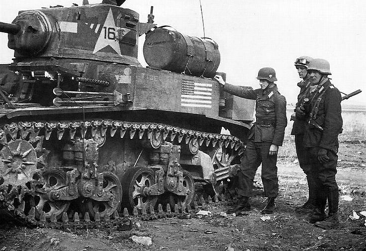 German soldiers inspect a knocked-out Stuart.
