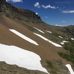 Bighorn Sheep ram crossing snowfield (second snowfield up from bottom of pic)