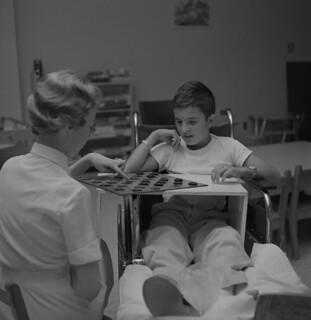 Nurse Shirley Olivier plays checkers with a young patient / L'infirmière Shirley Olivier joue aux dames avec un jeune patient