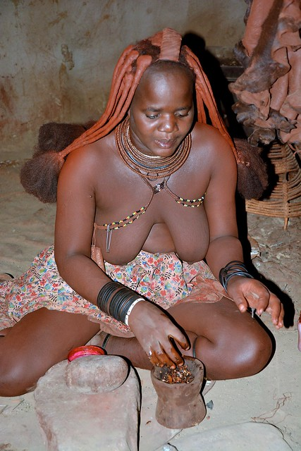 Himba girl mixing the ochre makeup - a traditional make up session!