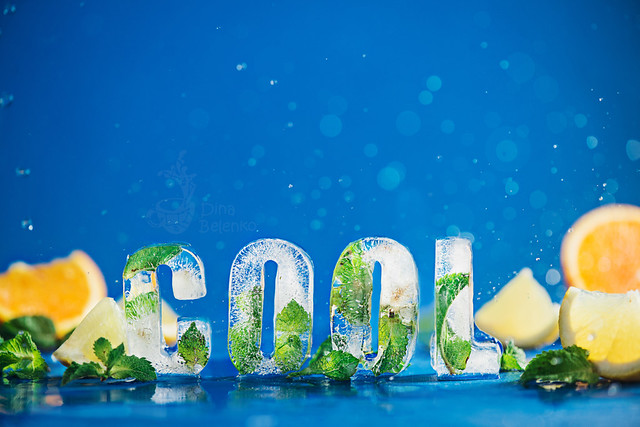Ice cube lettering with frozen mint leaves, lemon slices and oranges on a blue background with water splashes. Text says Cool.