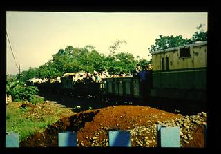 People Riding On A Train = 貨物列車に乗っている人々