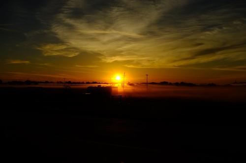 sunrise foggy orange light poles tank cart telephone line