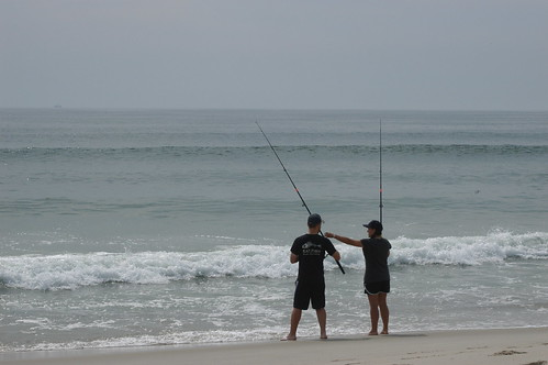 Photo of two people fishing in the ocean surf
