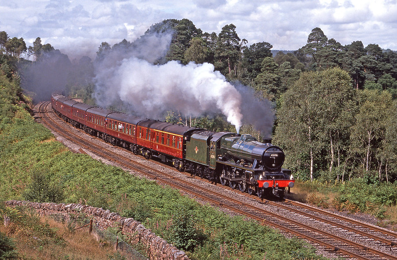 With 2 Jubilees on the main line at the moment carrying Red and Black liveries, here is a glimpse of what we are missing...Double chimneyed 45596 ' Bahamas ' passes through Barron Wood with a southbound Cumbrian Mountain Express on the 17th August 1989. The area south of Armathwaite known as Barron Wood was once very popular with photters for both North and South bounds trains back in the 80'S and 90's. Unfortunately we were not very popular with the landowners and it is a while since I have seen a shot taken in this location, I am not even sure if it still on due to tree growth, such a shame.  Pentax Spotmatic. Fuji RDP 100.