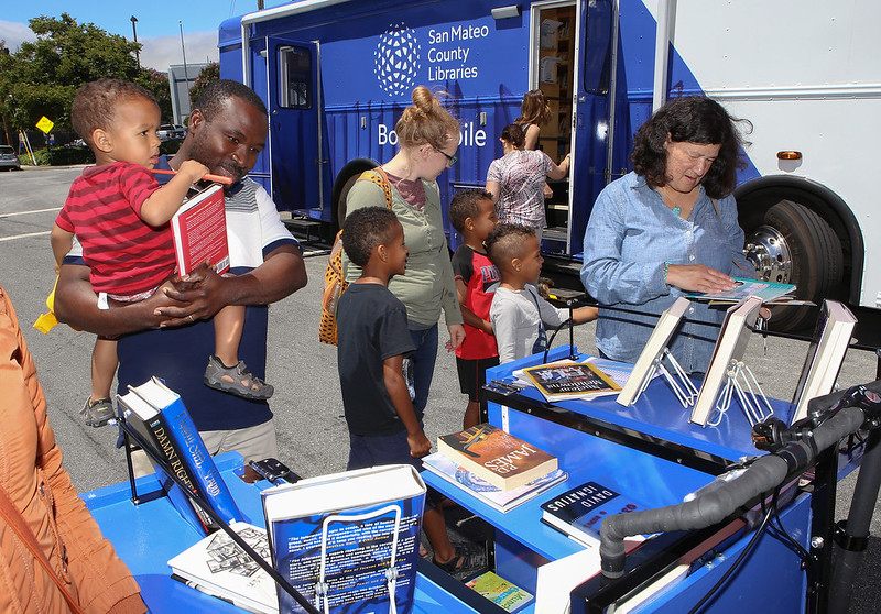 Patrons viewing books on the book bike.