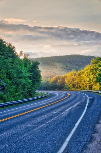d5100 nikond5100 2017 nh new highway wet lakewinnipesaukee alton glow sunset light orange gold trees hills mountains lines curve clouds sky day evening mist