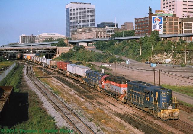CONRAIL WESTBOUND TRAILVAN TRAIN ROLLS THROUGH TOWN BEHIND BANGOR & AROOSTOOK GEEPS - CLEVELAND, OHIO - AUGUST 1976