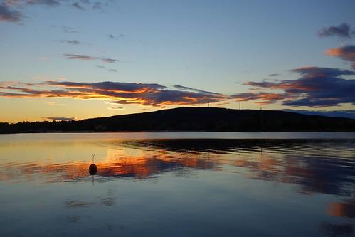 water sky lake sunset sun clouds reflections mountain hills