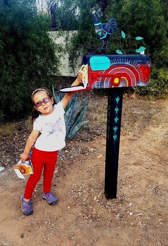 Ibis Funk-Weyant, 4 year-old Broadmoor neighbor, reaching into the Poetry Mailbox. (Urban Poetry Pollinators)