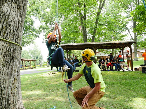 Photo of Natural Resources Careers Camp student using ropes to climb a tree