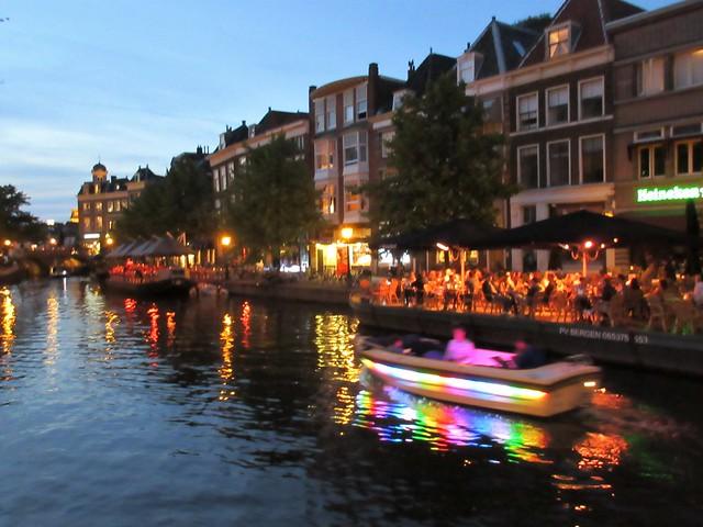 Boat with rainbow lights on Nieuwe Rijn at dusk, Leiden, Netherlands