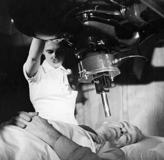 A nurse is giving cancer treatment to a patient using x-ray therapy / Une infirmière utilise un appareil de radiographie pour traiter un patient souffrant d'un cancer