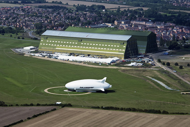 Worlds largest flying machine: Airlander 10 Hybrid Air Vehicles airship outside the Cardington Sheds - aerial image