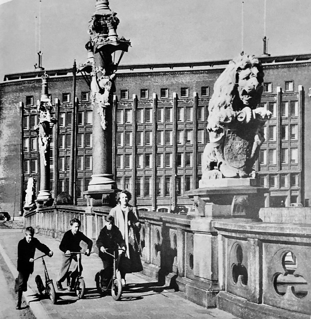 Children waking on Regentessebrug at the Wijnhaven in 1950's. I can't identify building on a background
