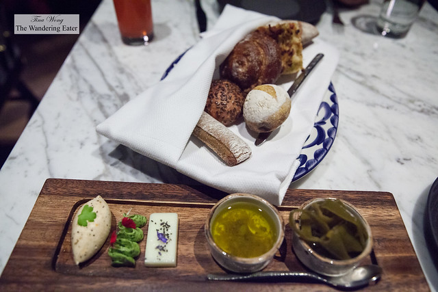 Large bread service with Oaxacan honey butter, herb butter, goat milk butter, leek caper anchovy oil amd pickled peppers