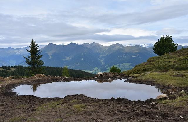 una pozza d'acqua riflette il cielo grigio