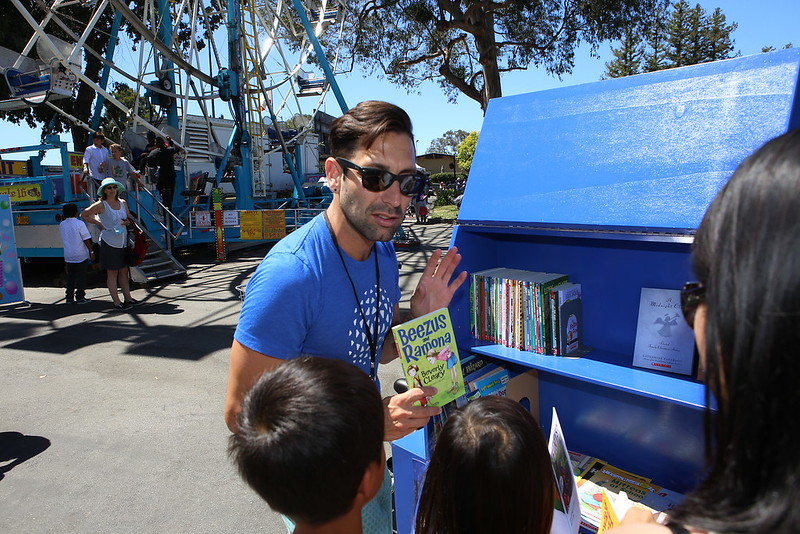 SMCL staff showing children books from the book bike.