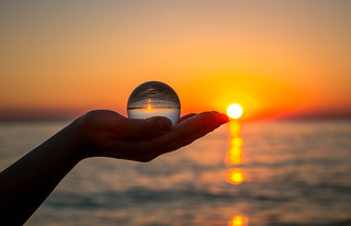 Glass ball in girls hand during sunset | by wuestenigel