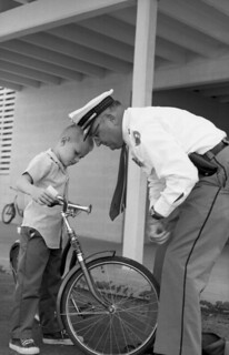 Lloyd Mitchell having his bicycle inspected by TPD Sgt. Sid Keller