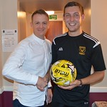 Matchball sponsor Chris Porter (left) is presented with a signed ball from Huntly goalscorer Michael Clark
