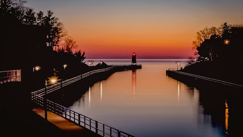 dusk evening low exposure long michigan lamppost railing shadows orange sky color reflections water sea seascape lake river pier lighthouse light sunlit sundown sunset sun greatphotographers