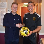 Michael Clark (right) presents a signed ball to Charles Stewart from Rigmarine