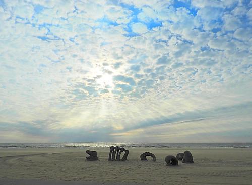 dinosaur bones sand sky clouds sun rays sea waves ocean city maryland