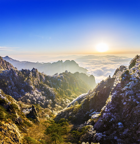 china huangshan yellow mountains sunrise trees forest morning frost ray rays fog mist dew chinese asia asian top world heaven clouds ice blue sky