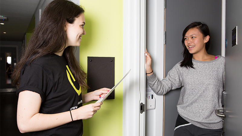 A student opening the door of their accommodation to a Hall Rep